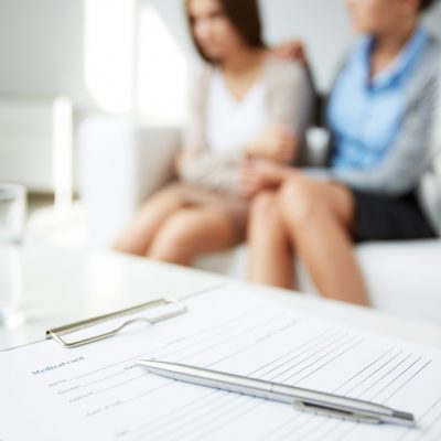 Image of medical card with pen on background of psychiatrist comforting her patient